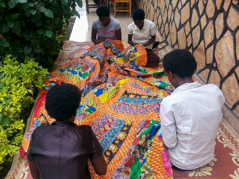 The women of Tubahumurize sewing one of their beautiful quilts